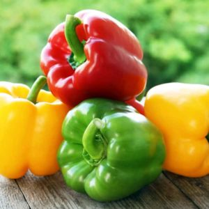 red, yellow, green bell pepper on wood table