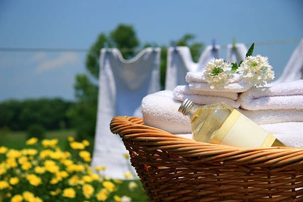 wicker basket of clean linen in front of a clothesline