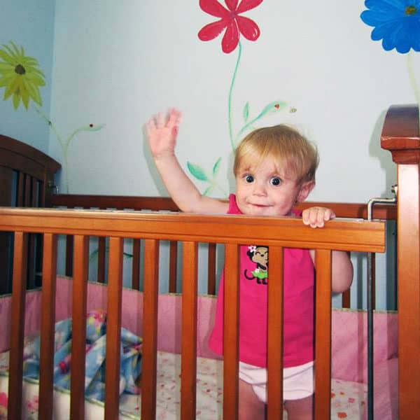 toddler waving from crib with flowers painted on the wall in background