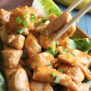closeup of orange chicken on wooden bowl with chopsticks