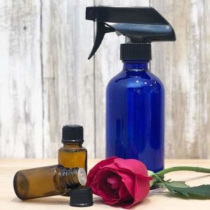 blue glass spray bottle, two essential oil bottles, rose