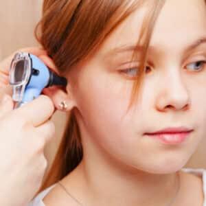 girl having ear examined with otoscope