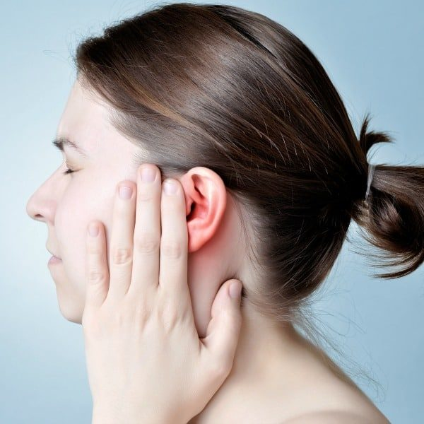 woman holding painful ear