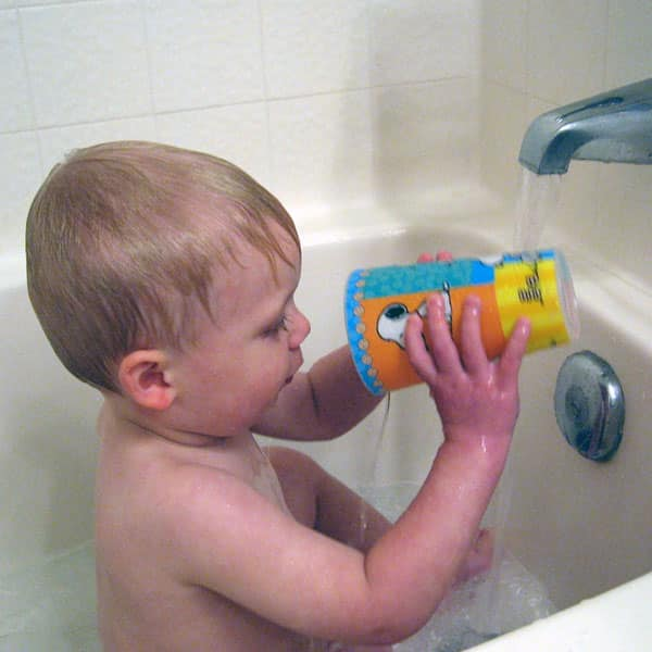 kid pouring water in the bathtub