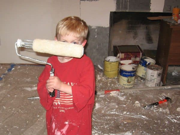 little boy in messy room with paint roller