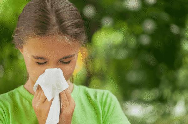 girl sneezing into kleenex