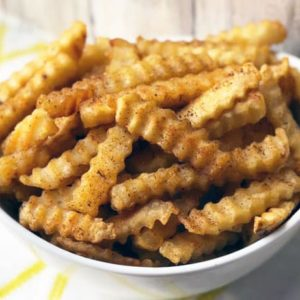 close up of cooked french fries with seasoning