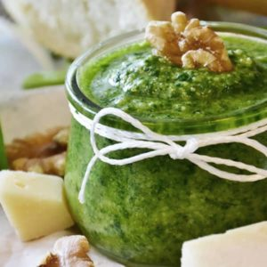 glass jar full of pesto with walnut on top