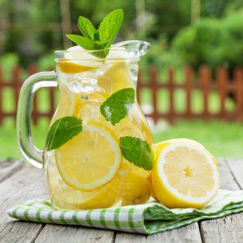 large glass pitcher full of lemonade and lemon slices