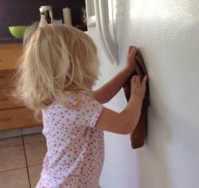 toddler wiping down fridge