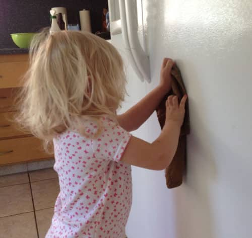 toddler wiping down fridge