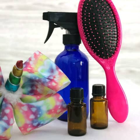 hair bow, spray bottle, hairbrush, essential oil bottles