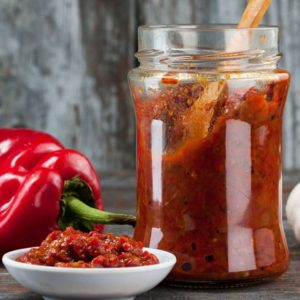 closeup of glass jar with hot sauce and wooden spoon