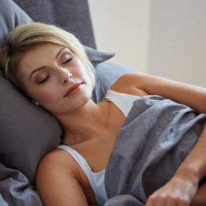 blonde woman sleeping in bed on gray pillows