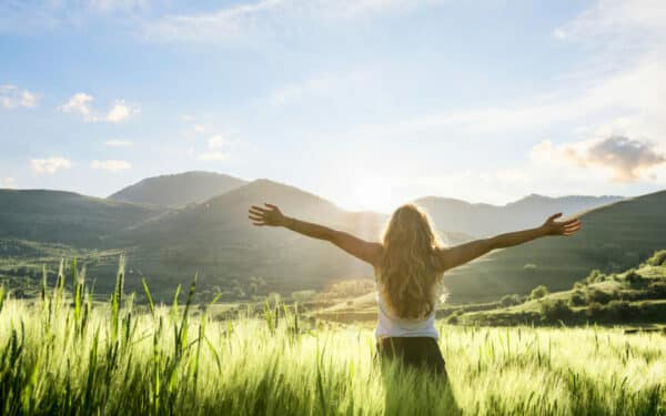 woman in field, arms outstretched