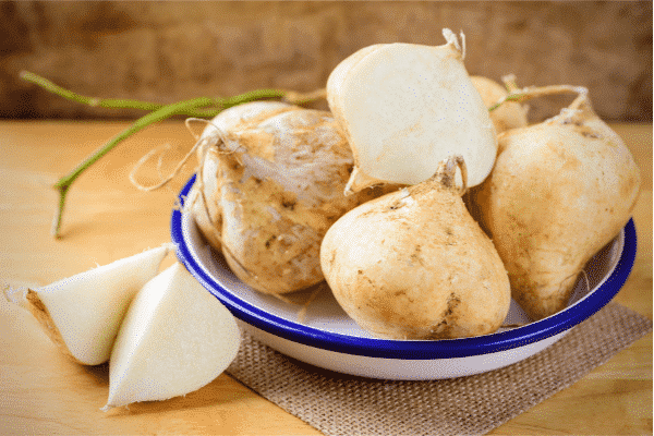 whole and cut jicama in a bowl
