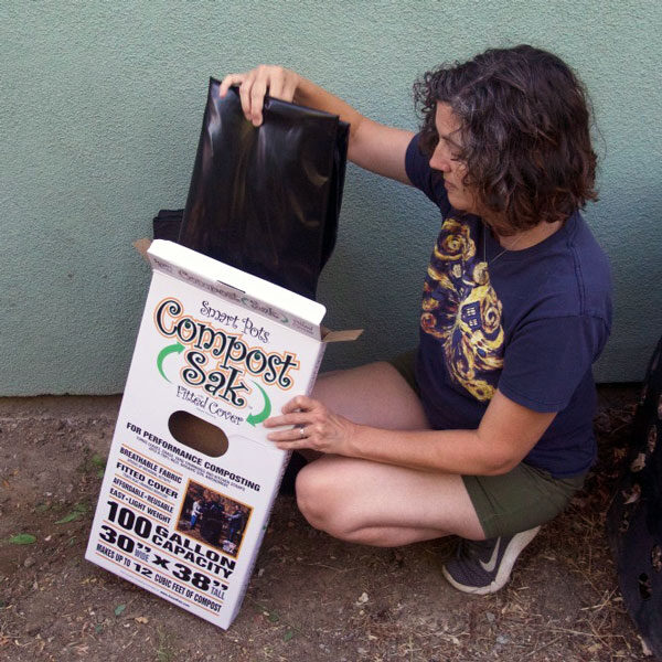 woman removing compost sak from box
