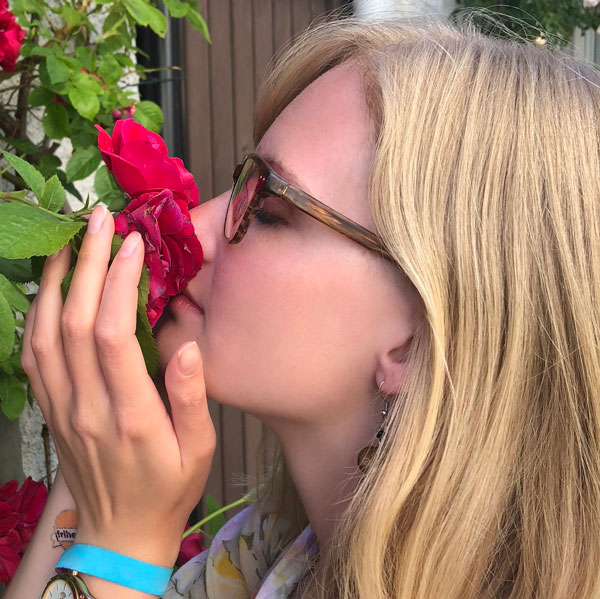 blonde woman smelling red rose bush