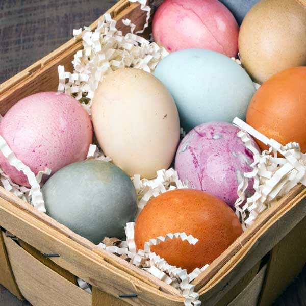 close up of colorful naturally dyed easter eggs in wicker basket