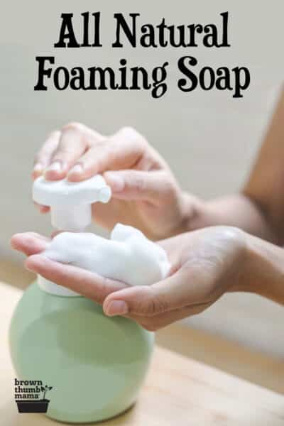 closeup of woman dispensing foaming hand soap from green ceramic container