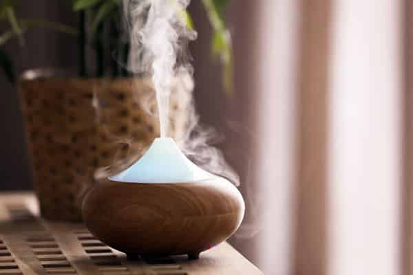elegant wood essential oil diffuser emitting steam on wood table