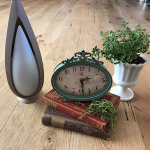 essential oil diffuser, antique clock and books with thyme plant