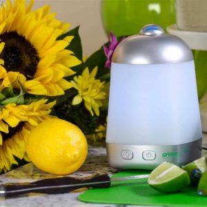 pyramid shaped essential oil diffuser on table with sunflowers and fruit