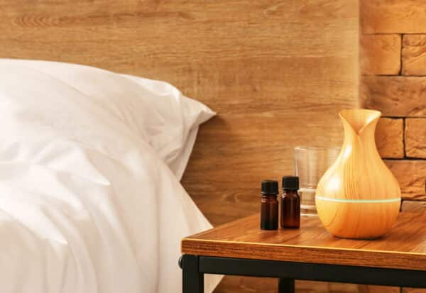 essential oil diffuser and bottles by bed