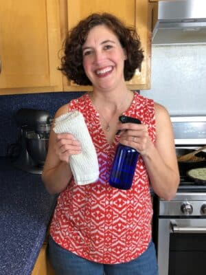 woman smiling in kitchen holding cloth and spray bottle