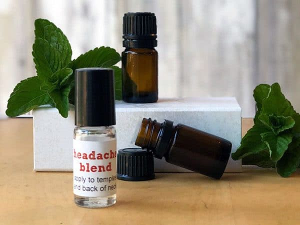 Essential oil bottles and mint leaves on a white box