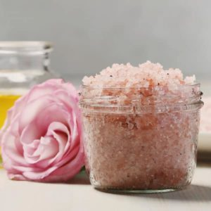 closeup of canning jar with pink bath salts and pink rose