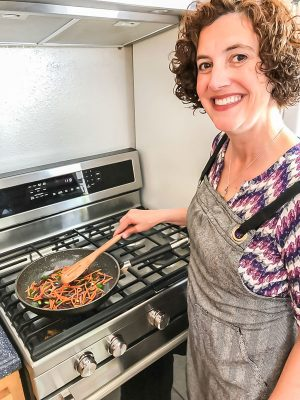 woman smiling and cooking stir fry vegetables at stove