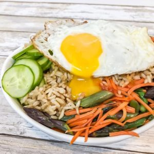 brown rice bowl with vegetables and runny egg over top