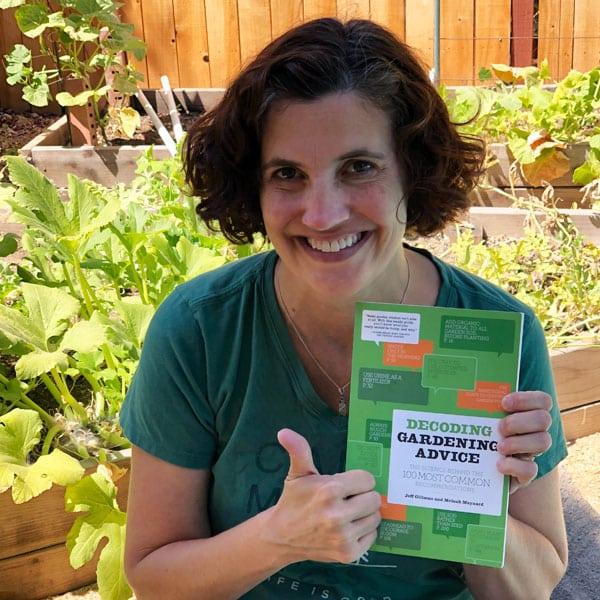 smiling woman holding gardening book