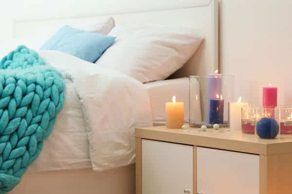scented candles on table next to bed