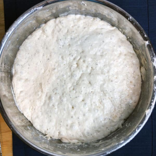 bread dough after rising in a metal bowl