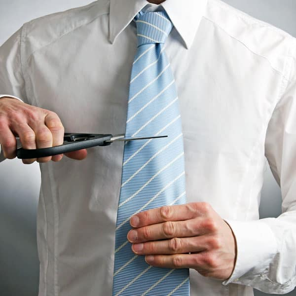 man cutting necktie with scissors