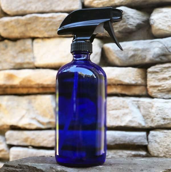 blue spray bottle in front of rock wall