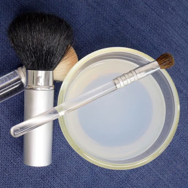 makeup brushes with bowl of castile soap cleaner