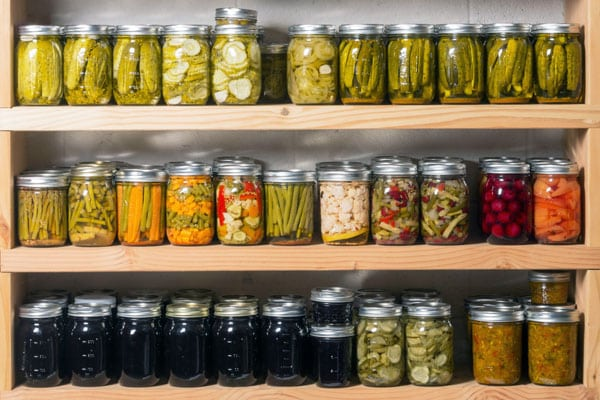 rows of canned vegetables and jelly in the pantry