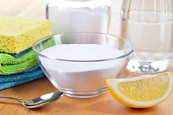 baking soda, vinegar, lemon, cleaning cloths on table