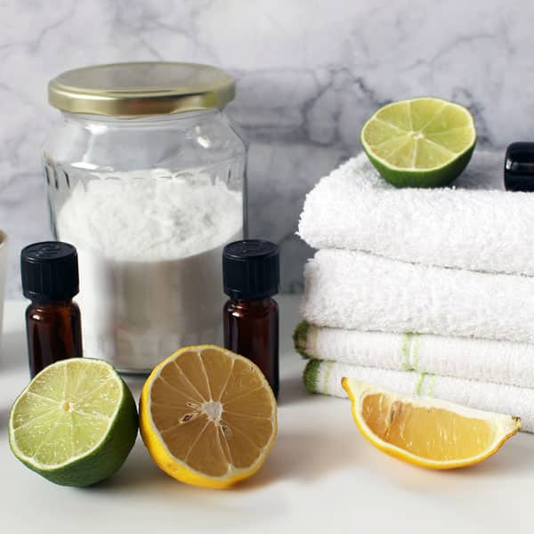 essential oils, lemon, lime, baking soda, cloths on white table