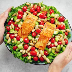 hands holding platter of salmon and tomato salad
