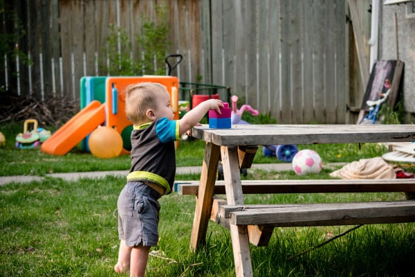 toddler grabbing blocks from outside table
