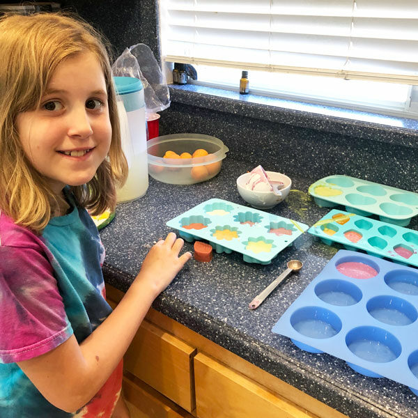 little girl with soap molds on counter
