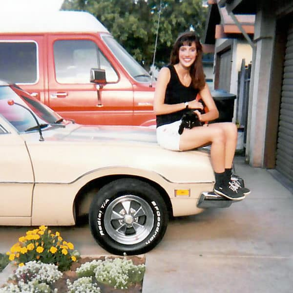 woman sitting on hood of car