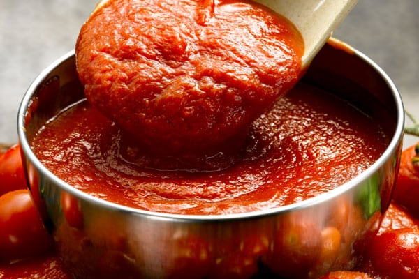 bowl of tomato sauce with spoon